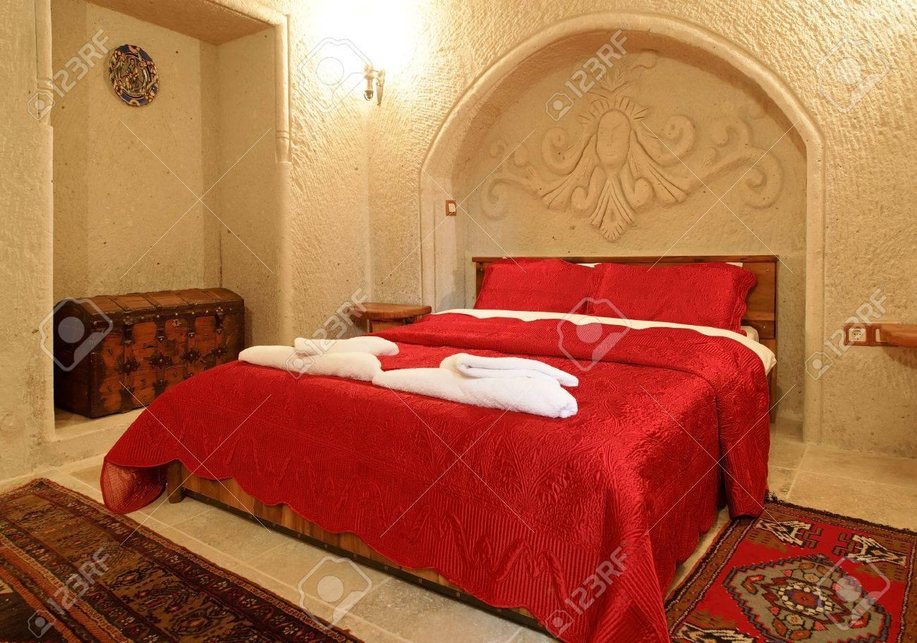 L\'intérieur des détails architecturaux d\'une chambre avec alcôve et arcade  avec des couvre-lit détaillant, dans Couvre-lit brodé rouge vif et taies ...
