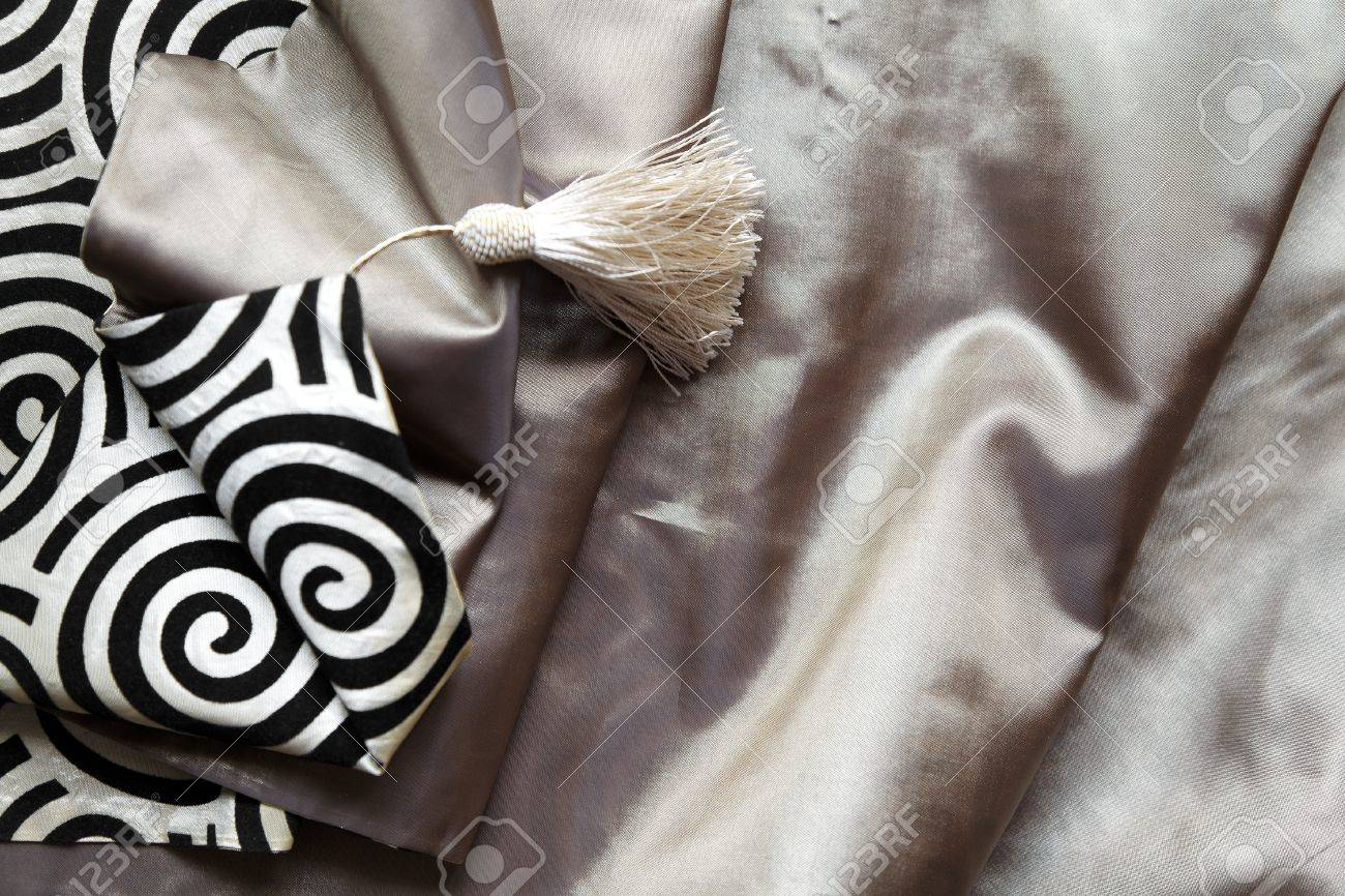 landscape portrait of black and white twirls and tassle on a light colored silk textile with copy space and crop margins Stock Photo - 11146039