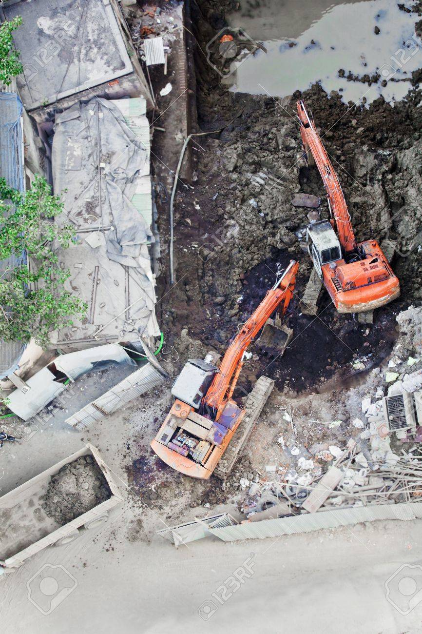 Construction site in Mumbai, India, two diigers working together to move soil onto a tipper truck, aerial view Stock Photo - 13302031