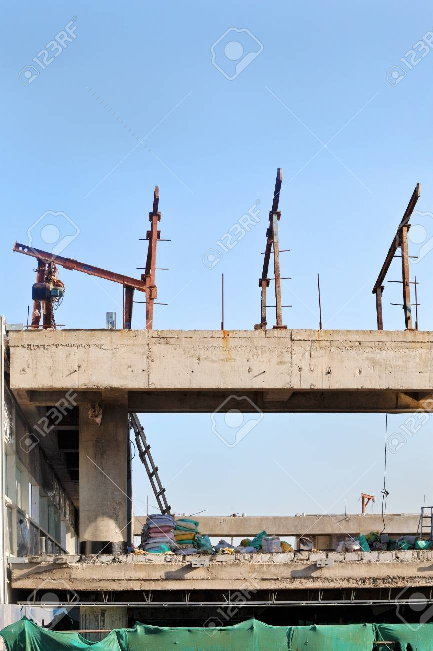 Vertical take of a construction site with lifting gantries on the upper floors for materials handing  Dry, bright day with clear blue sky Stock Photo - 16713239