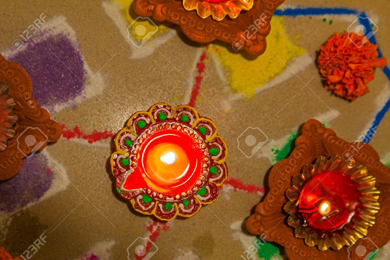 Color portrait and overhead capture of rangoli and diva candles which are hindu hinduism symbols and signs of celebrations and auspiscious occassions such as Divali Holi New year weddingd and family celebrations  Generic hindu image captured in Bombay Ind Stock Photo - 21421831