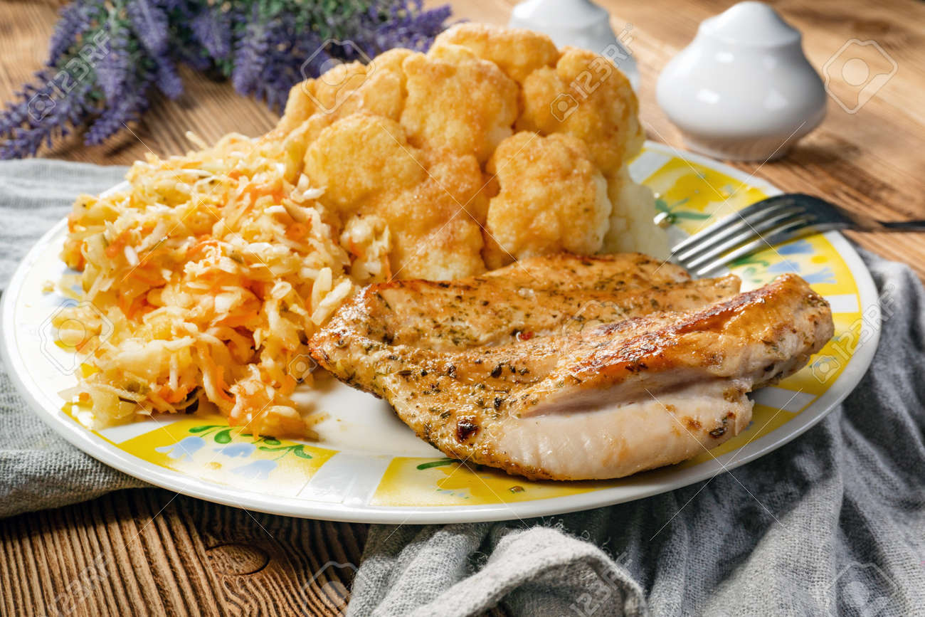 Fried chicken served with boiled cauliflower and salad. - 158096723