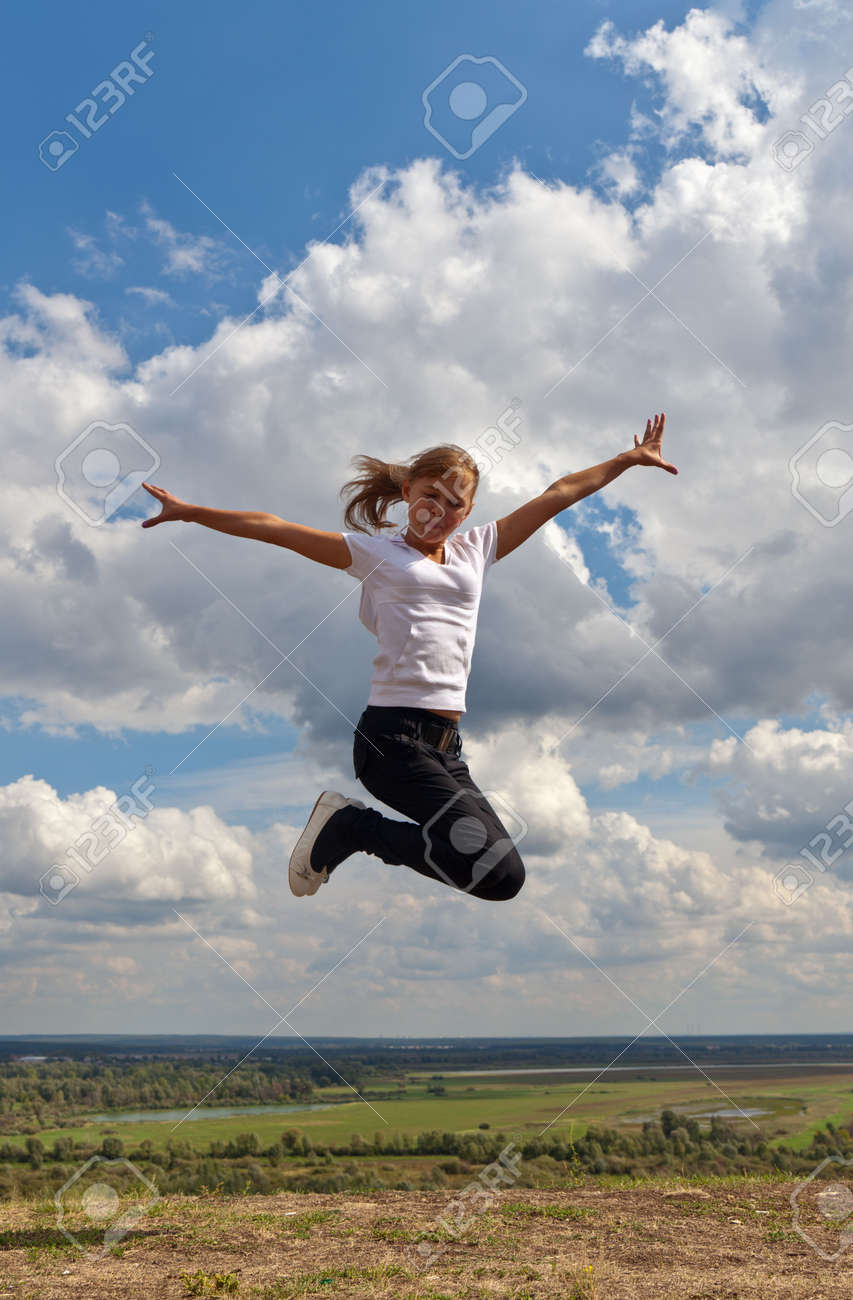 The girl in a jump on the nature in the summer Stock Photo - 7848493
