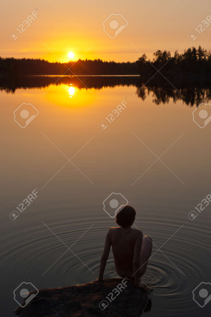 the woman is going to swim in the lake at sunset Stock Photo - 13208459
