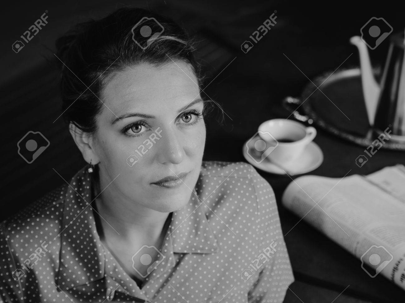 Stock photo vintage black and white portrait of a serious woman at tea time looking to the top retro style