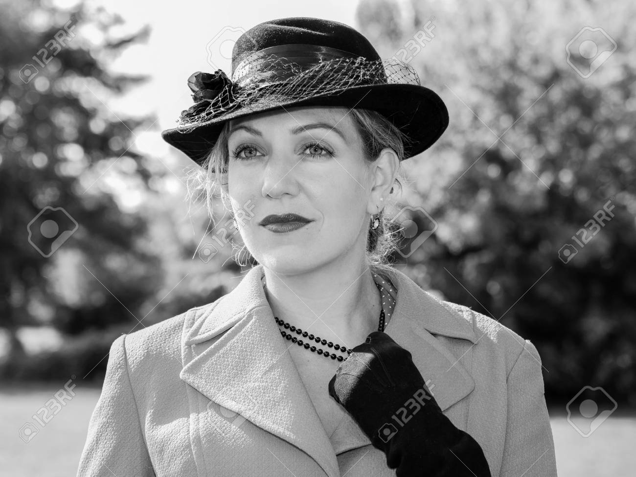 Stock photo vintage black and white portrait of a woman with a suit and a black hat looking dreamily