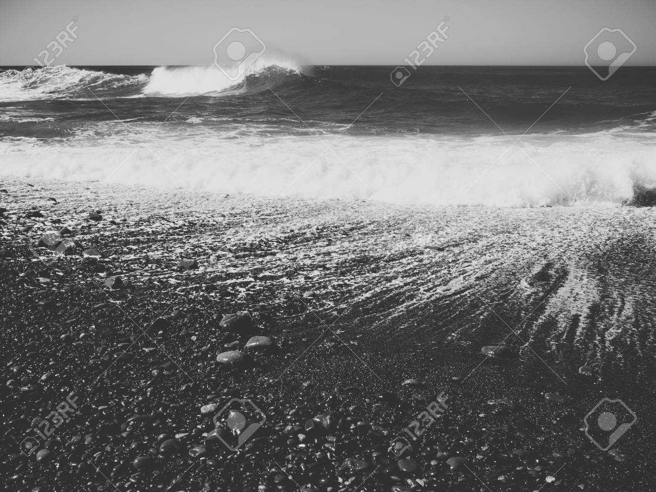 Seascape photo of a beach with dramatic waves black and white