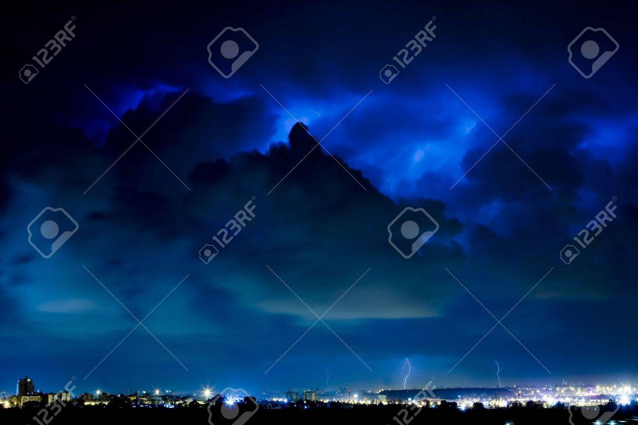 lightning storm in the night, dark-blue storm clouds over a lighted city Stock Photo - 2556092