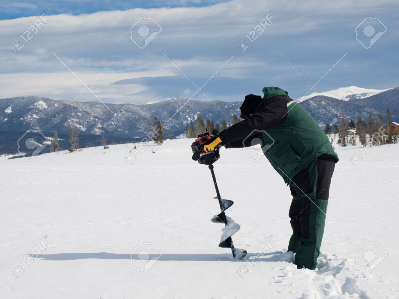 Fisherman eith an auger on the frozen lake Granby, Colorado. Stock Photo - 8918084