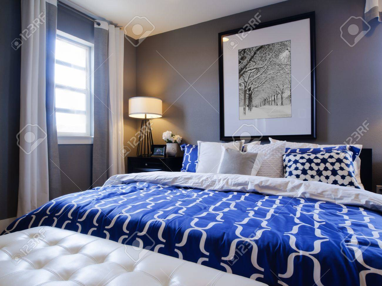 Modern Blue And White Bedroom modern master bedroom with blue wall and white linens. stock photo