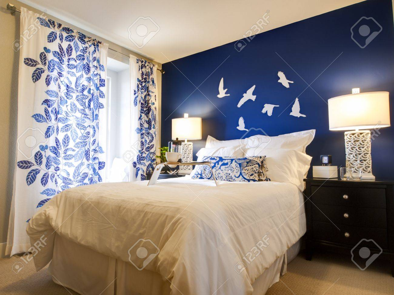 Modern master bedroom with blue wall and