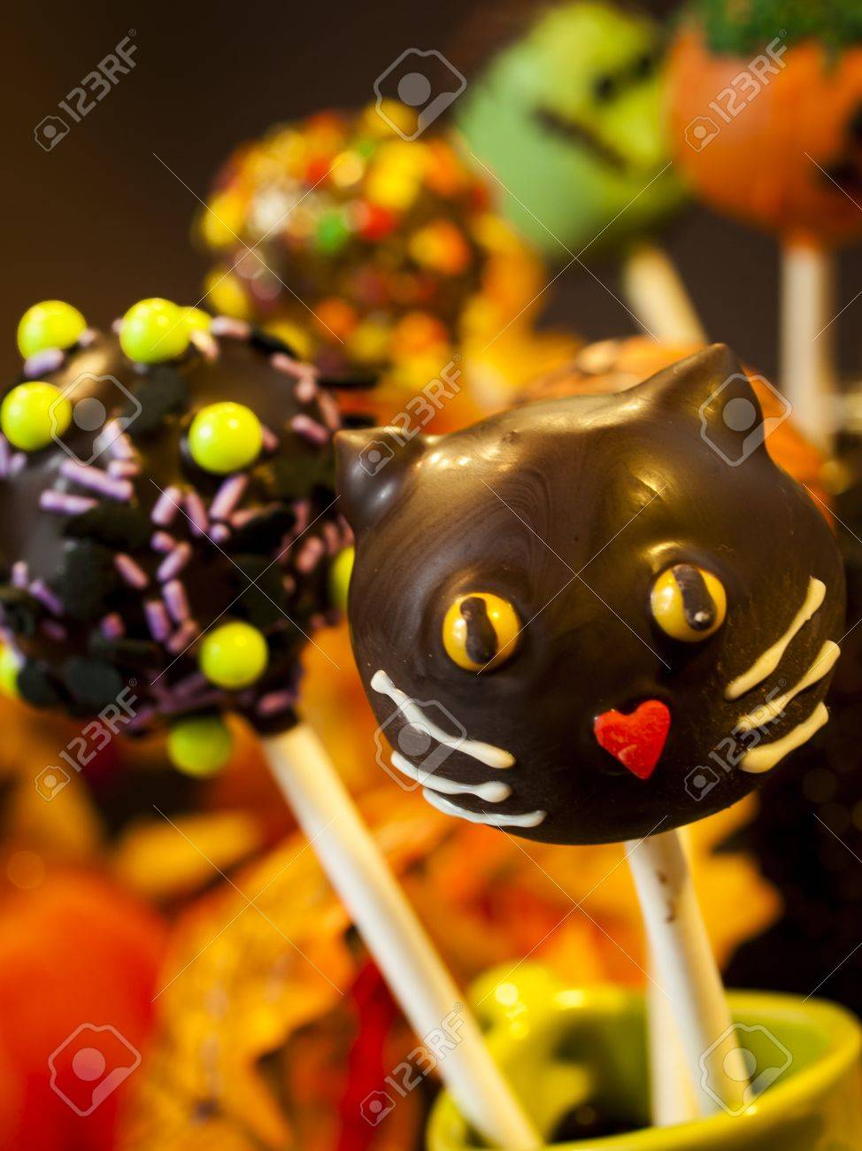 halloween gourmet cake pops with holiday decor on brown backround