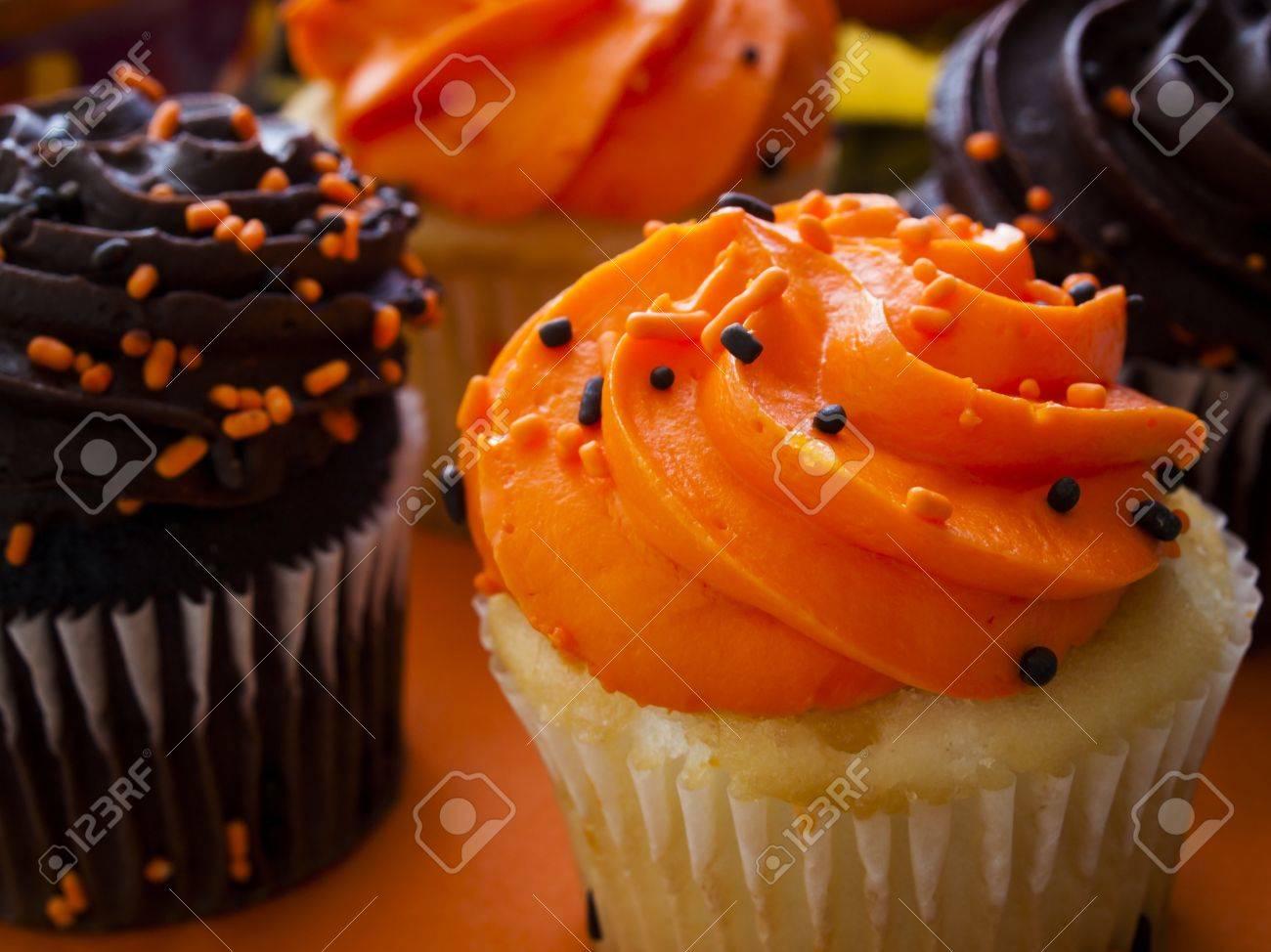 halloween cupcakes with orange and black icing on orange napkin