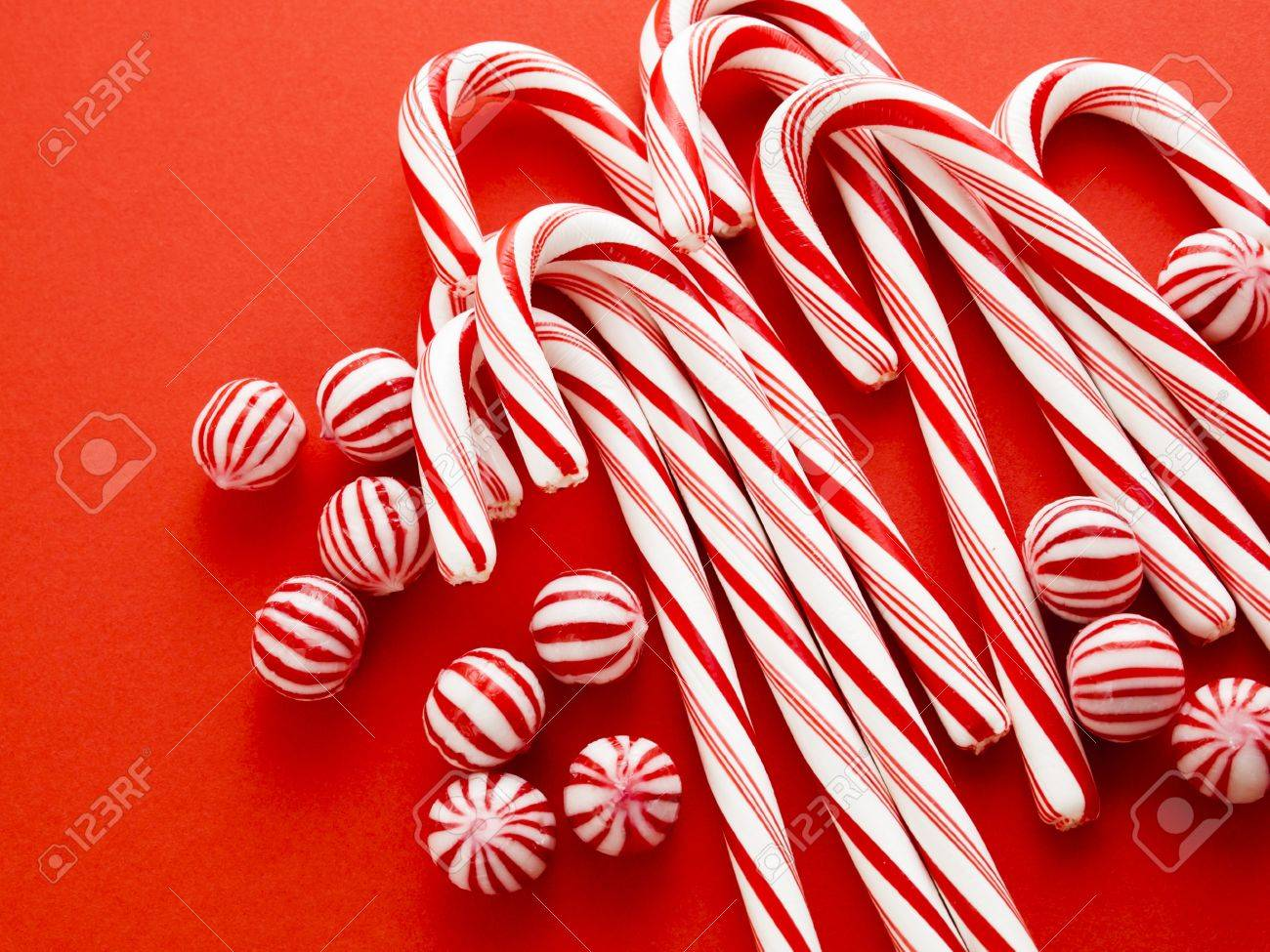 white and red peppermint candy canes on red background stock photo