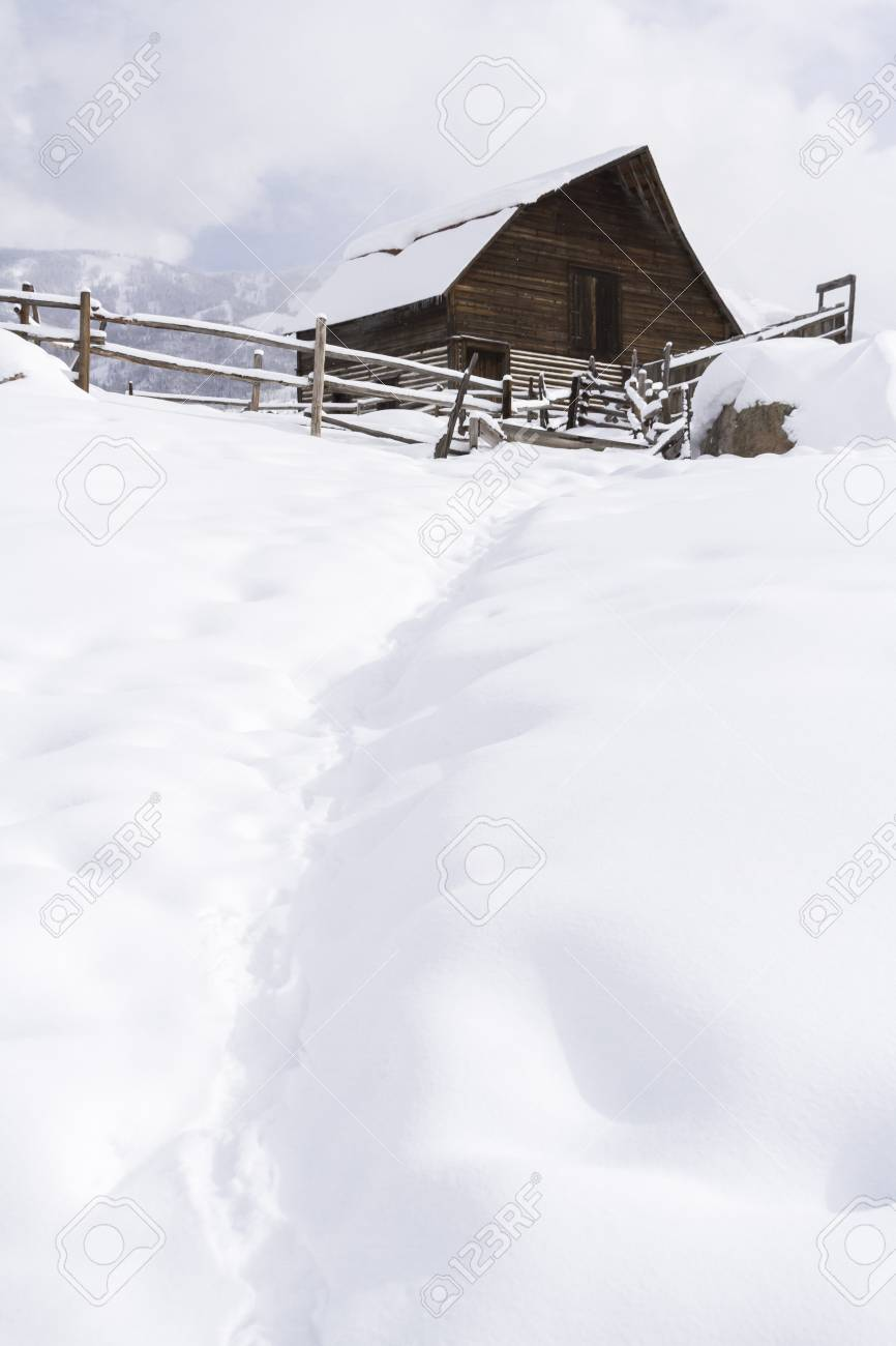 Aged barn on snowy hillside with ski lifts and ski slopes in background. Stock Photo - 17713012