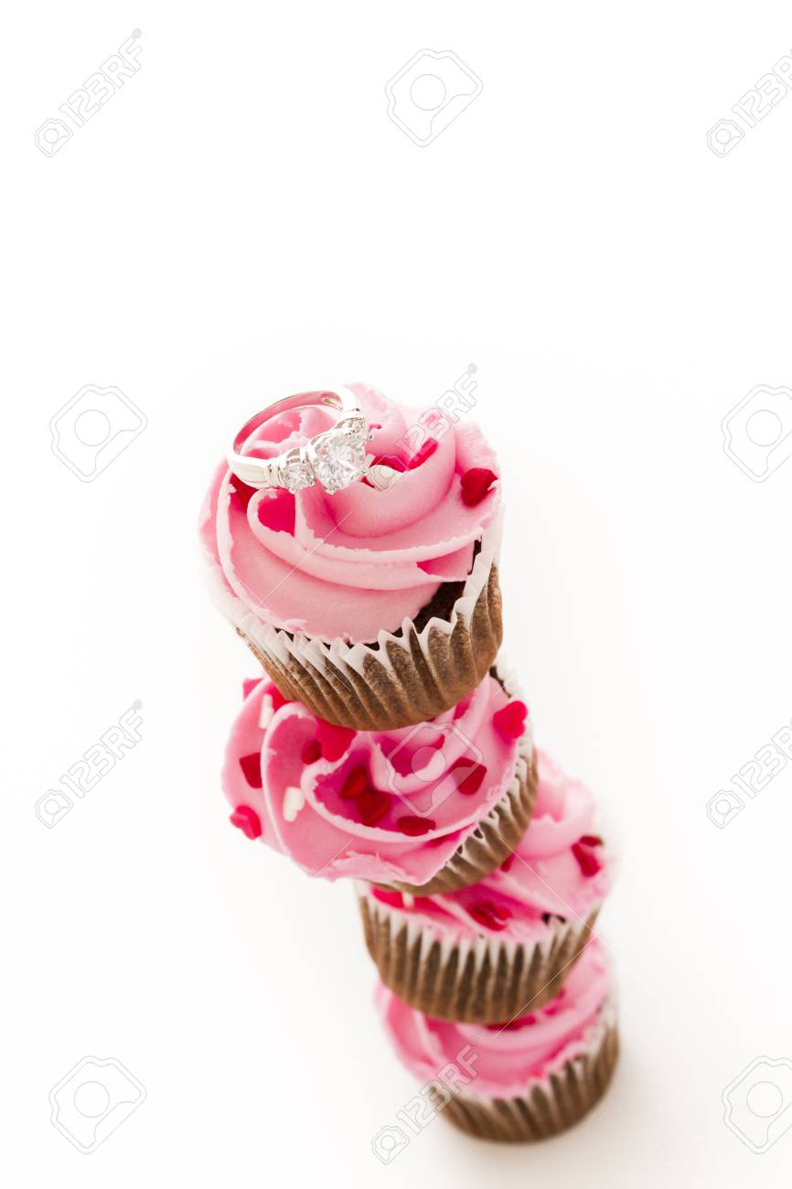 Stack Of Pink Cupcakes With Engagement Ring On Top Stock Photo
