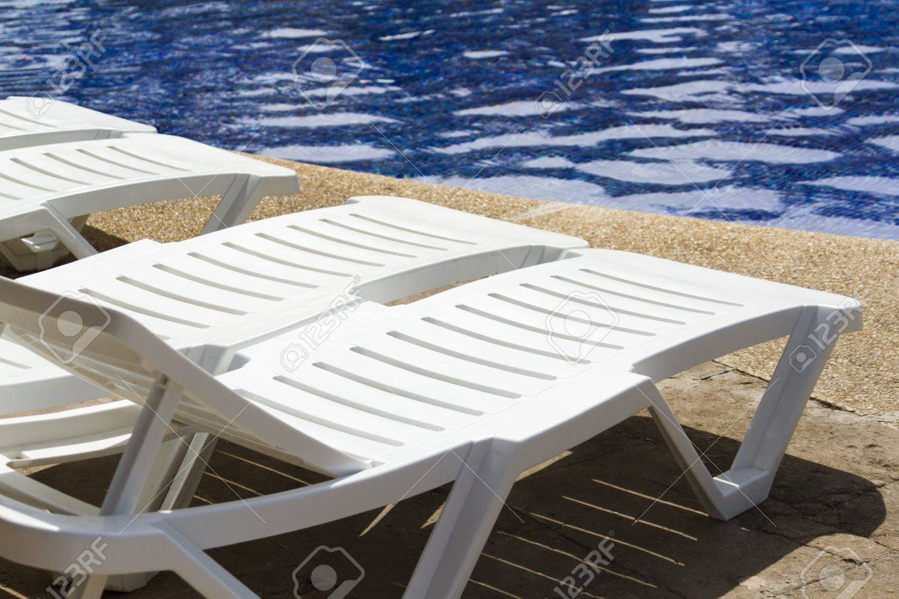 Stock Photo   White Plastic Pool Chairs At The Swimming Pool.