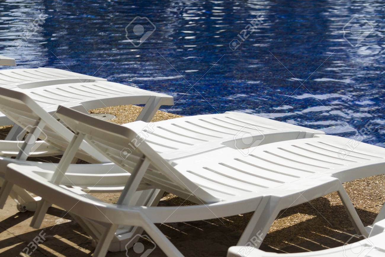 White plastic pool chairs at the swimming pool.