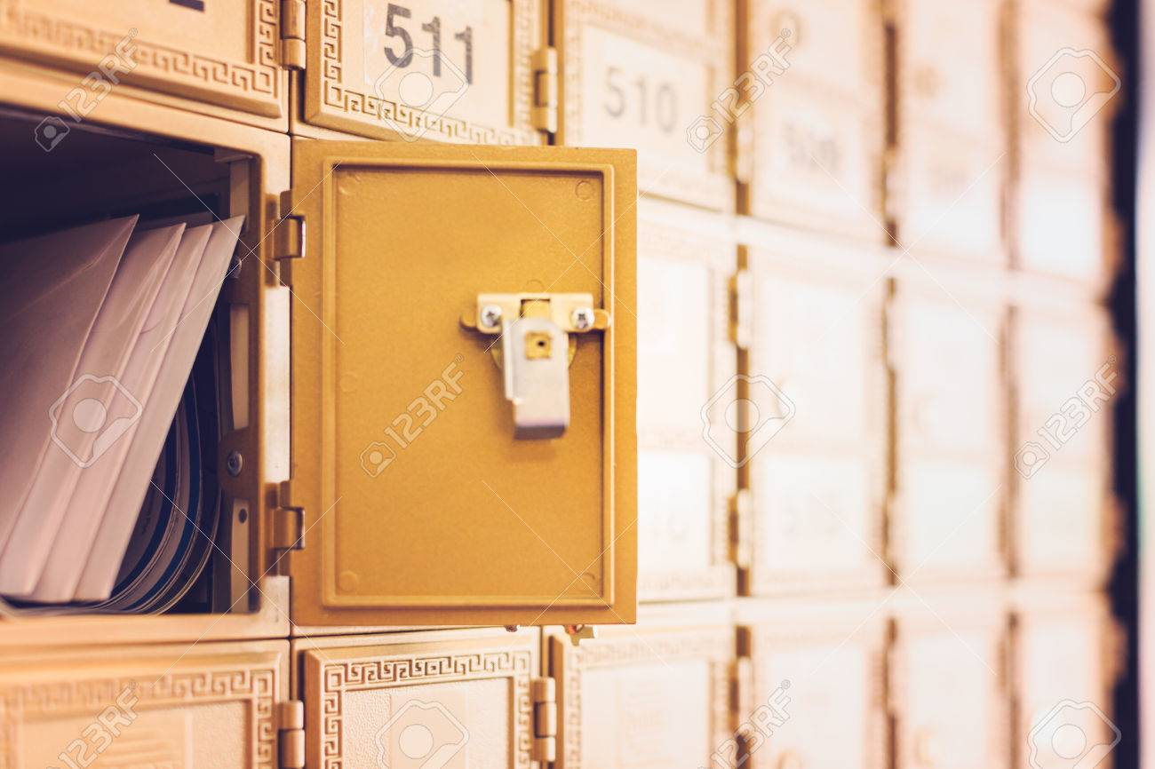 Rows of gold post office boxes with one open mail box Stock Photo - 29463242