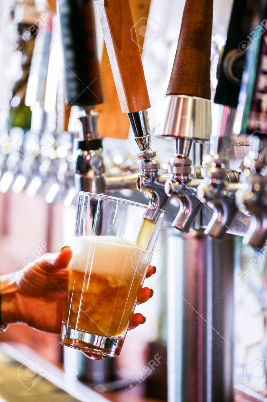 Bartender pouring draft beer in the bar. - 40793214