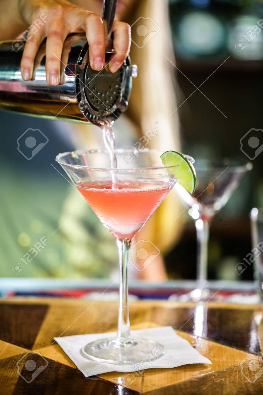 Bartender preparing Cosmopolitan drink for customer. - 40804415