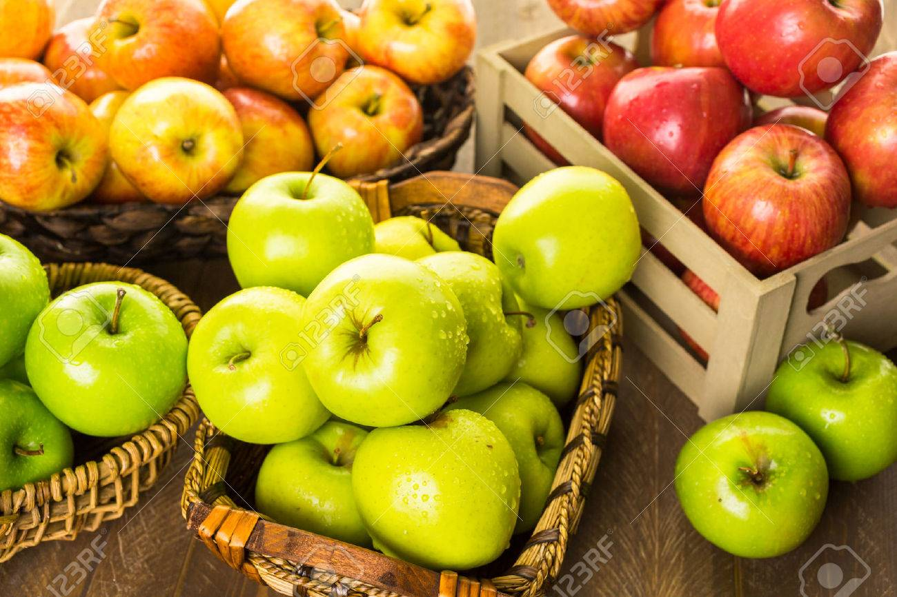 Variety of organic apples in baskets on wood table. Stock Photo - 45124268