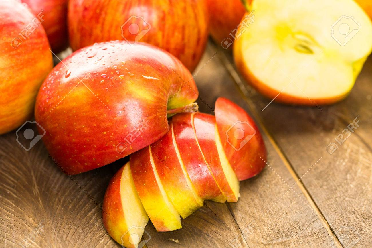 Variety of organic apples sliced on wood table. Stock Photo - 45124841