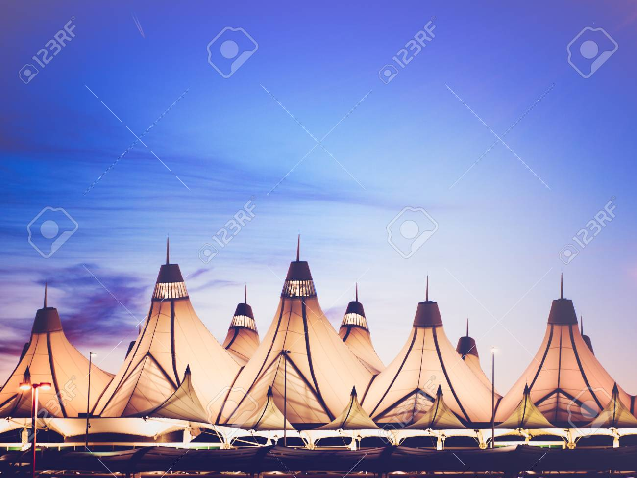 Glowing tents of DIA at sunrise. Denver International Airport well known for peaked roof. Design of roof is reflecting snow-capped mountains. - 47941995