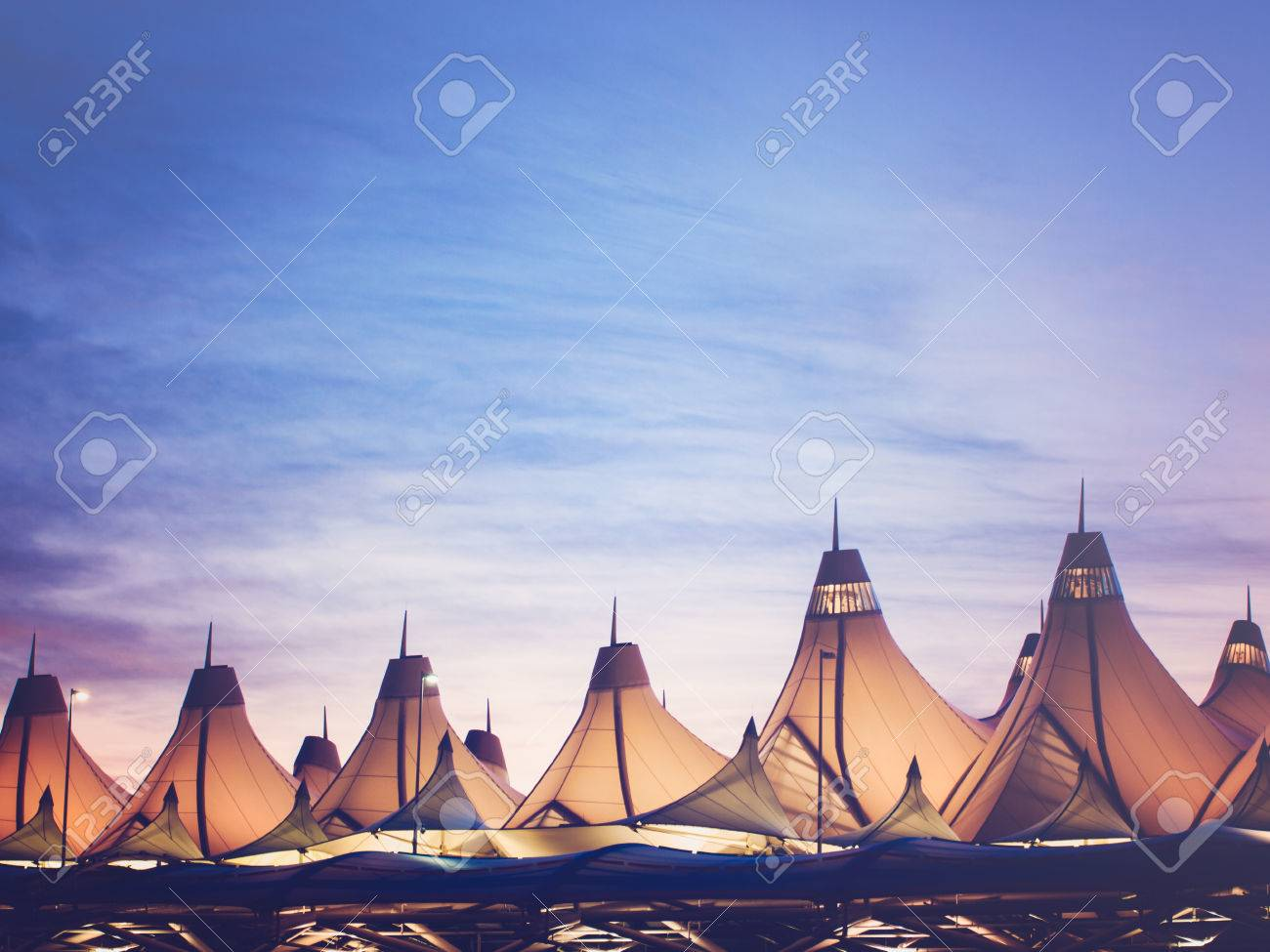 Glowing tents of DIA at sunrise. Denver International Airport well known for peaked roof. Design of roof is reflecting snow-capped mountains. - 47942071