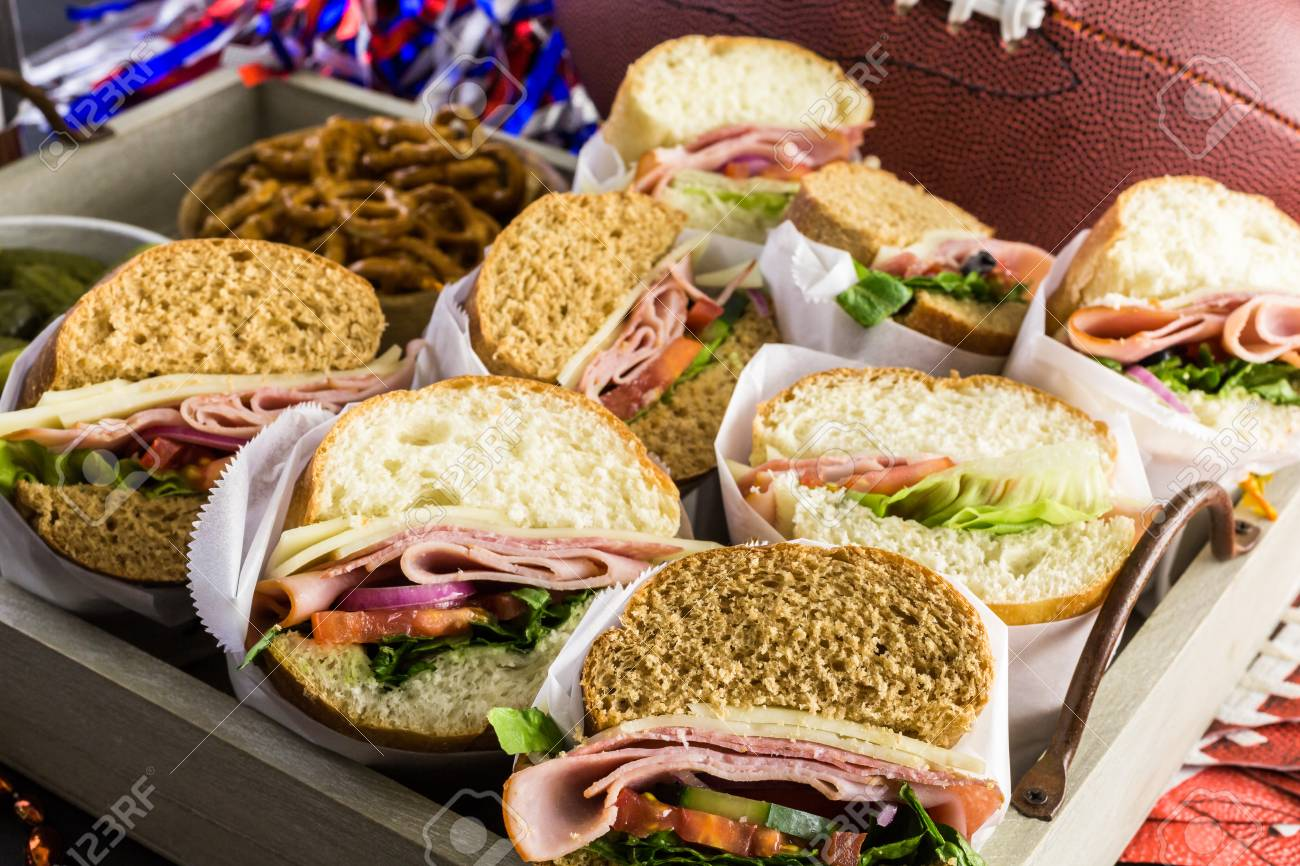 game day football party table with sub sandwich and snacks stock