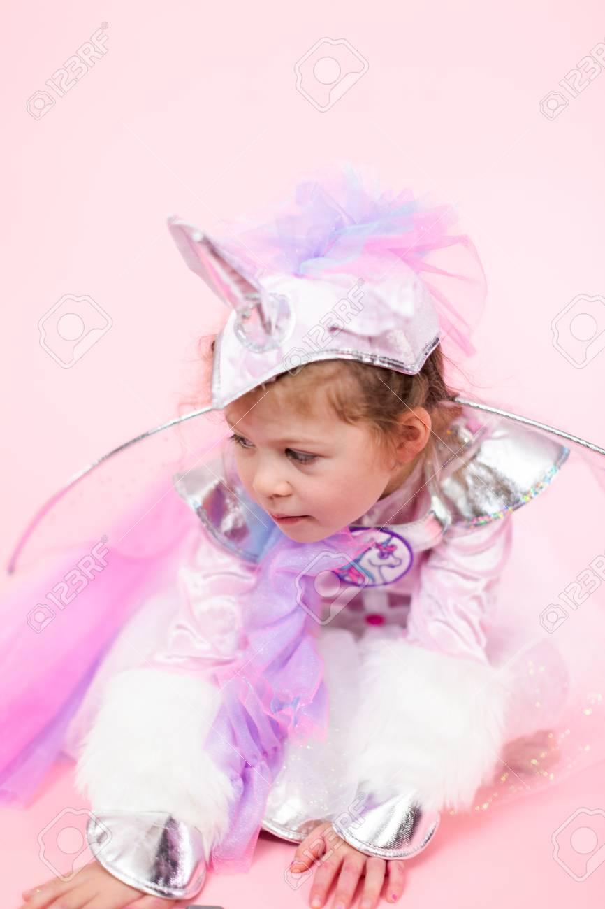 Portrait Of A Little Girl In Glitter Unicorn Costume On Pink Stock