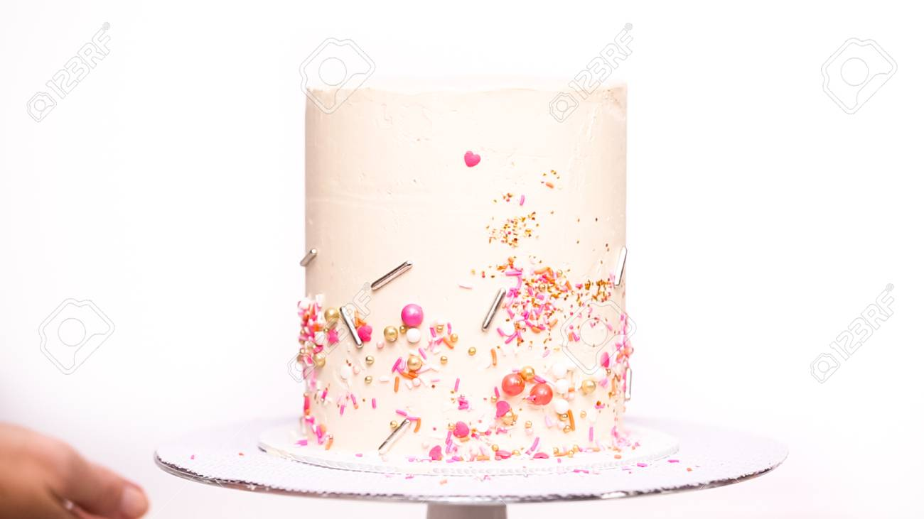 Decorating Tall Birthday Cake With A Pink Sprinkles Stock Photo