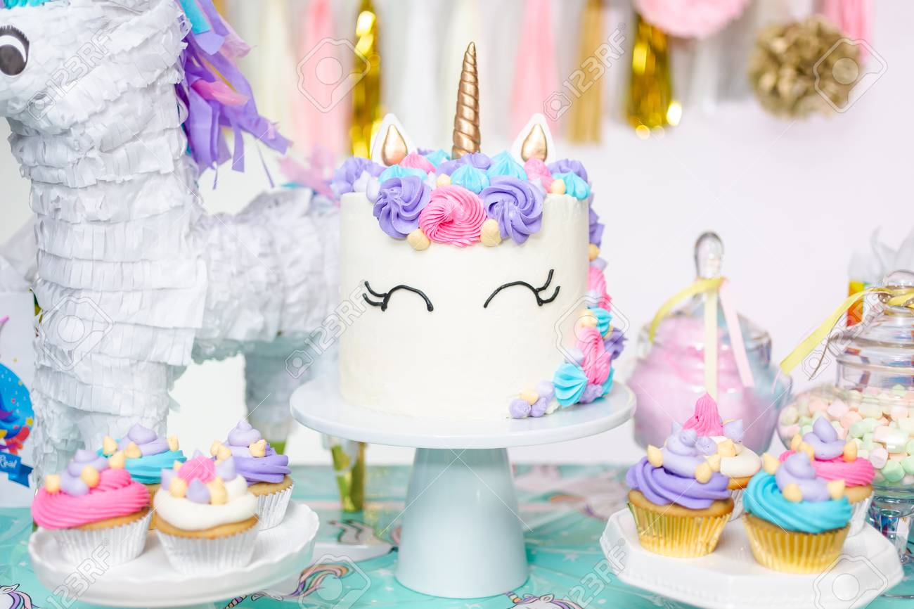 Little Girl Birthday Party Table With Unicorn Cake Cupcakes