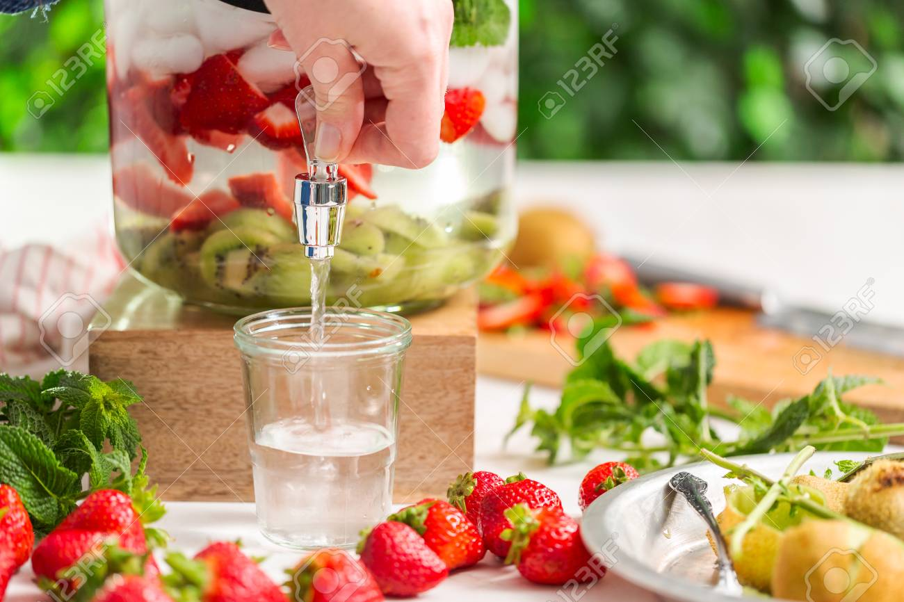 Pouring Infused Water With Organic Strawberries Kiwi And Fresh