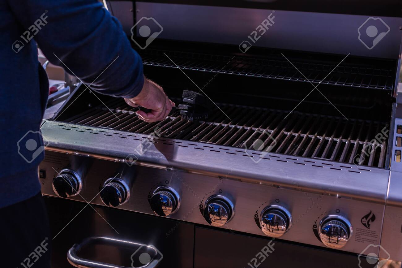 Cleaning BBQ grill for grilling meats. - 114177628