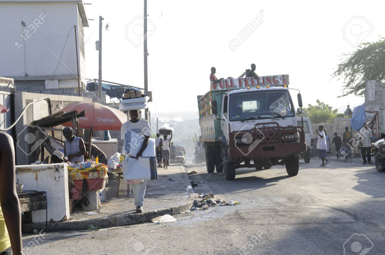 PORT-AU-PRINCE - SEPTEMBER 2: A man carrying plastics for the tents to be sold later on a busy early morning street in Port-Au-Prince, Haiti on September 2, 2010. Stock Photo - 18900580