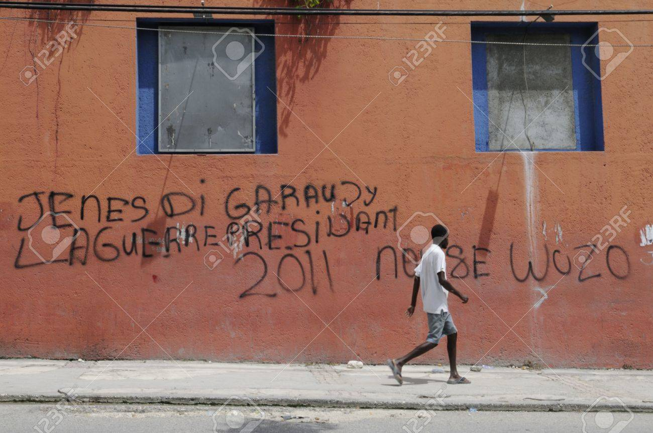 PORT-AU-PRINCE - AUGUST 21: A young man passing by a graffiti on the wall which supports the candidature of Wycleaf Jean as the President, in Port-Au-Prince, Haiti on August 21, 2010. Stock Photo - 18900610