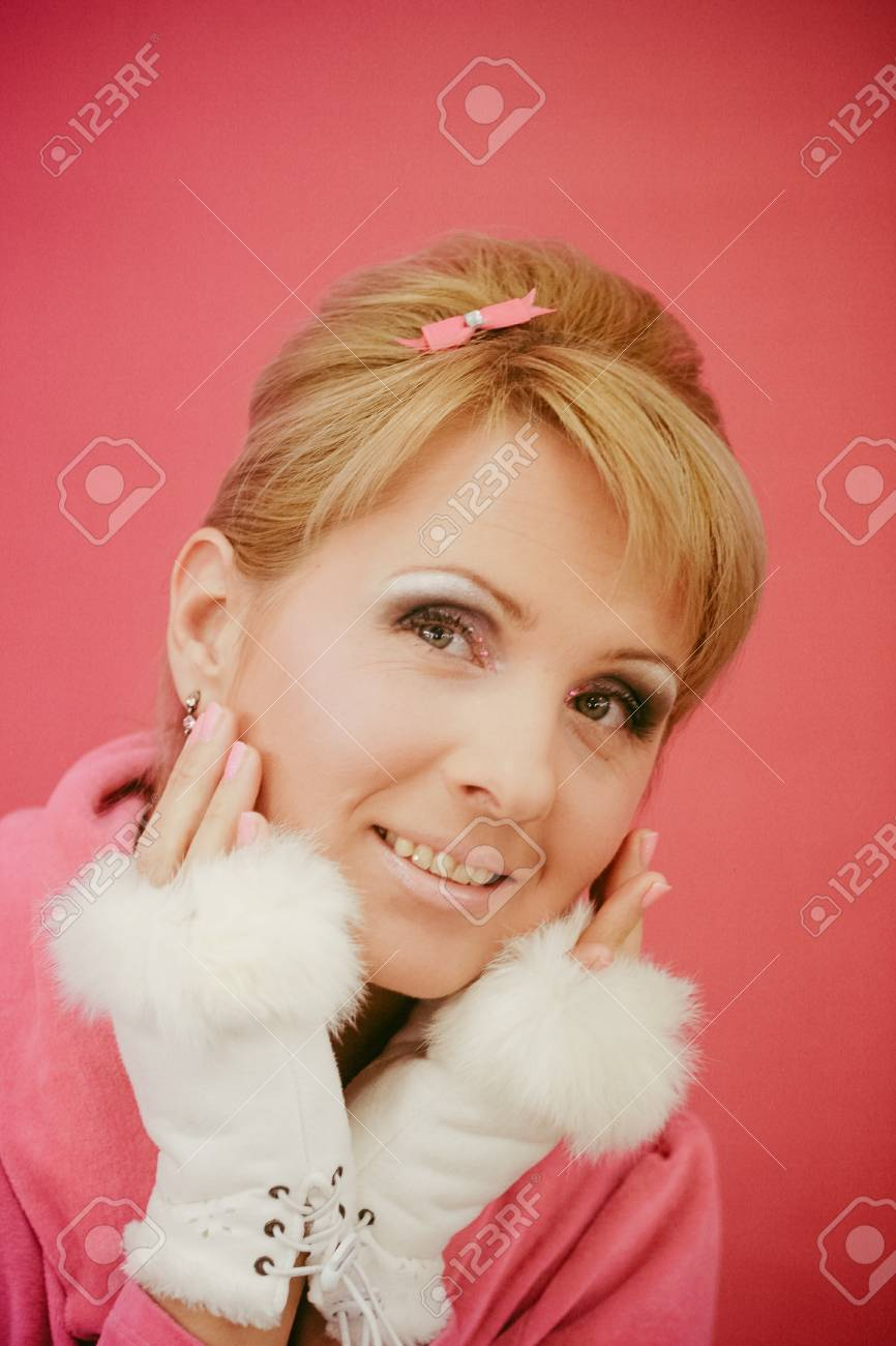 Closeup portrait of young beautiful women styled in pink 50s pin up style. Lady smiling cheerful and looking sides. Wearing white fluffy fur glows