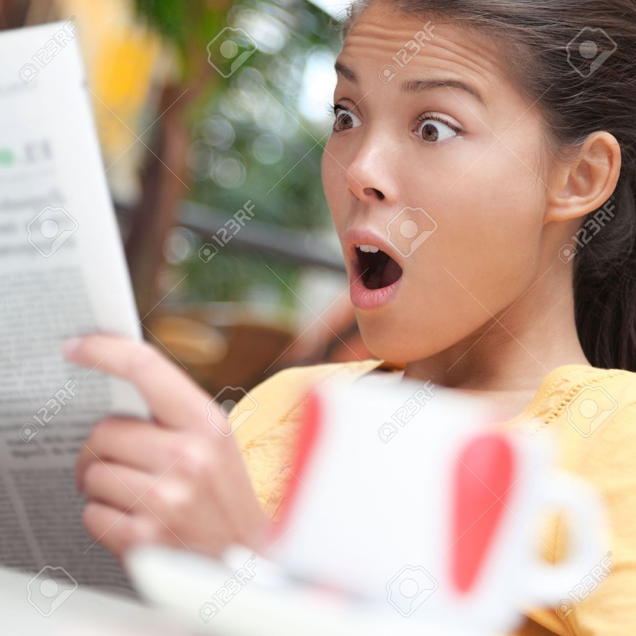 Woman shocked over shocking news in newspaper (gossip, stock market...). Young woman reading the paper on cafe outside. Stock Photo - 7439161