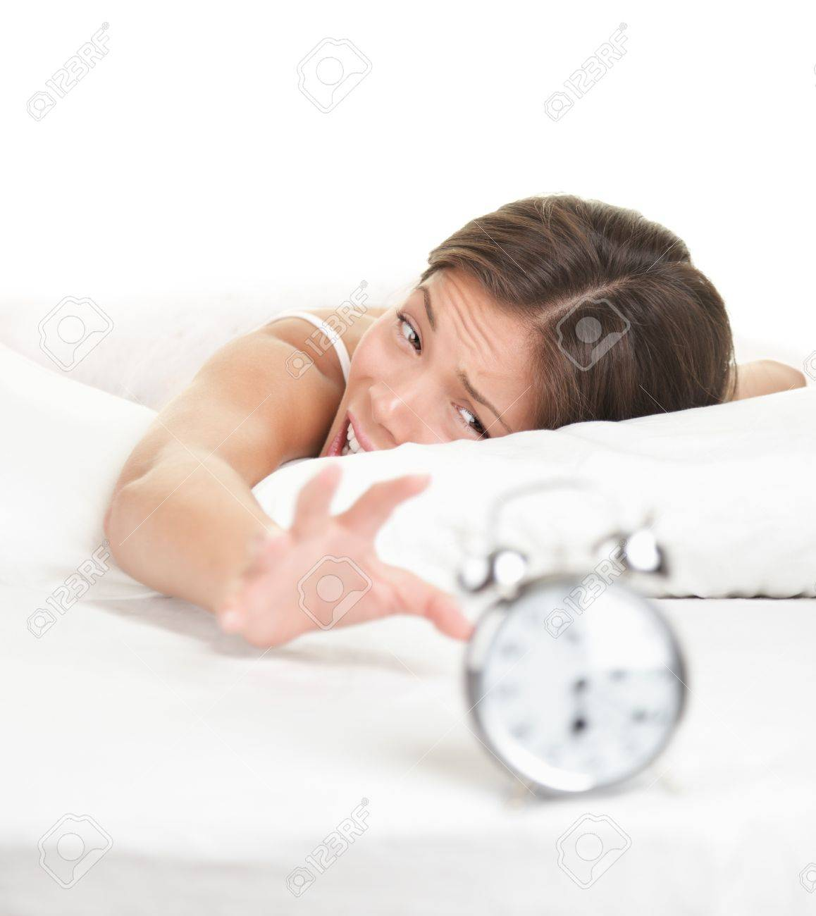 Woman and Alarm Clock. Funny image of woman lying in bed early in the morning. Isolated on white background. Stock Photo - 7439154