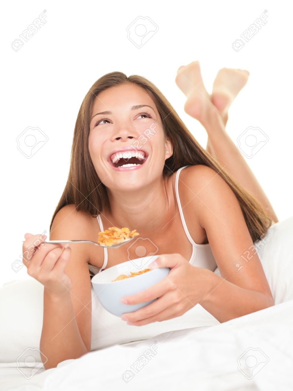 Woman eating breakfast in bed. Happy woman enjoying cornflakes cereals in the bed in the morning. Beautiful mixed race Chinese Asian / Caucasian female model lying in bed isolated on white background. Stock Photo - 7439163