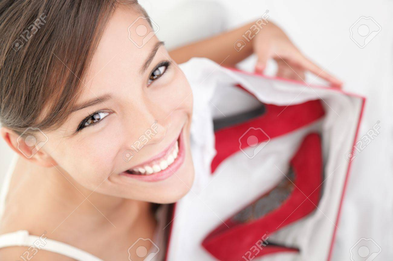 Woman getting shoes as gift or happy of her shopping. Asian woman surprised and happy to receive red high heels shoes as a present. Isolated on white. Stock Photo - 7439203
