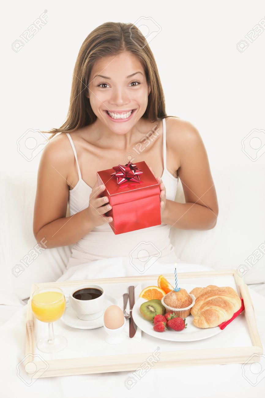 Birthday gift woman getting morning surprise in bed with present and breakfast. Young smiling excited and happy woman holding a birthday gift or a valentines day present. Stock Photo - 7780027