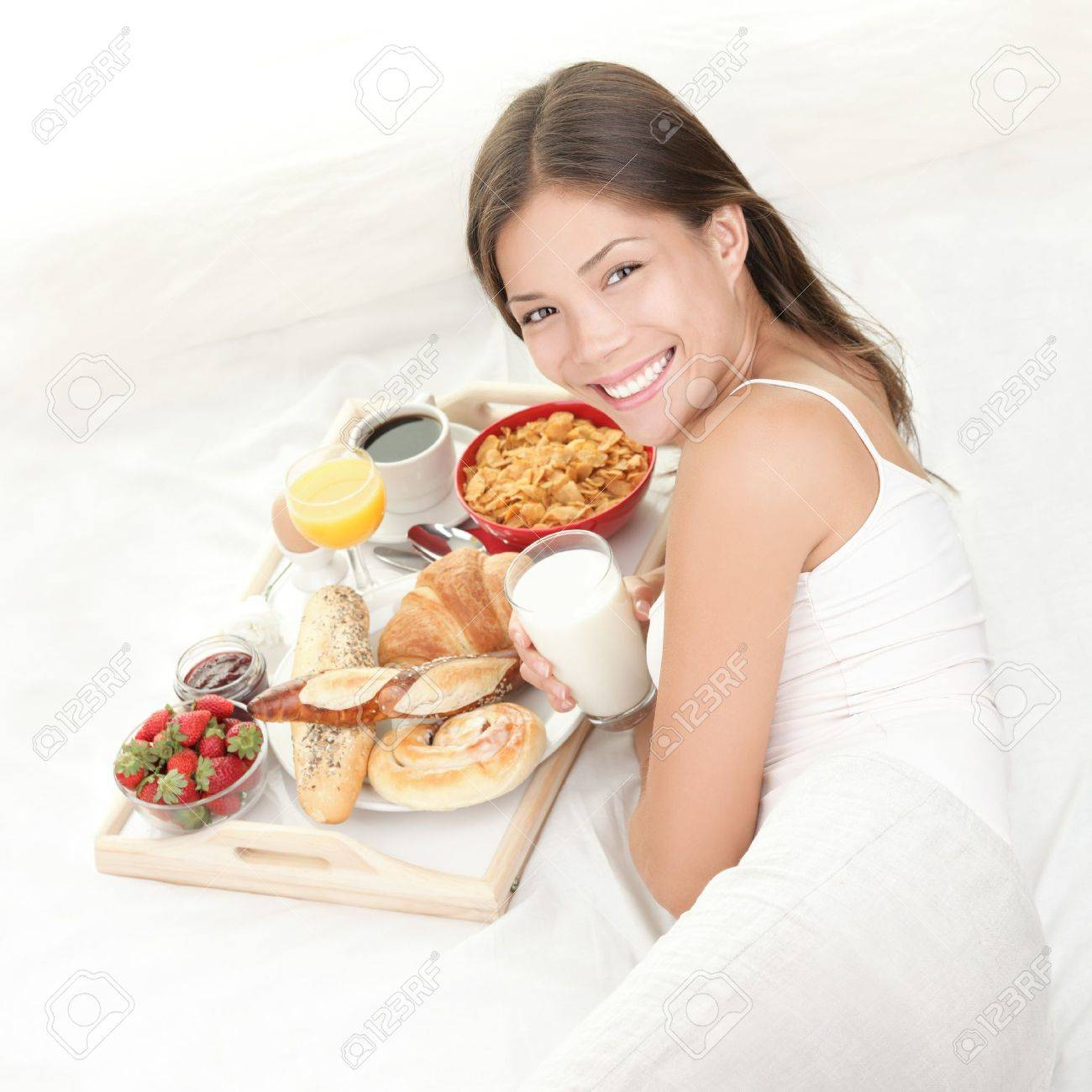 Breakfast in bed. Young woman eating breakfast in bed drinking milk. Beautiful young woman smiling. Stock Photo - 7780060