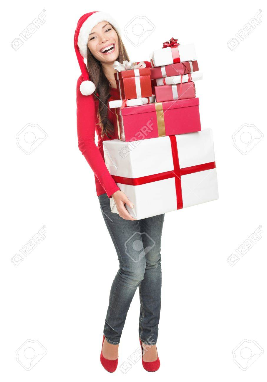 Christmas woman holding gifts wearing Santa hat. Standing in full body isolated on white background. Smiling woman portrait of a beautiful mixed Asian / Caucasian model. Stock Photo - 7989995