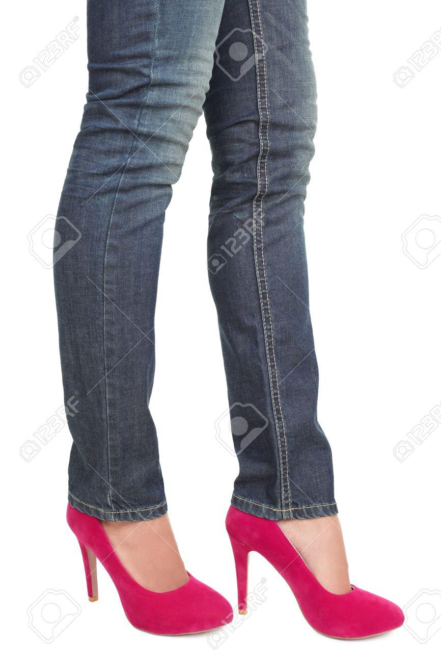 Donna in jeans e caldi rosa rosse tacchi. closeup della metà inferiore del corpo isolato su sfondo bianco.