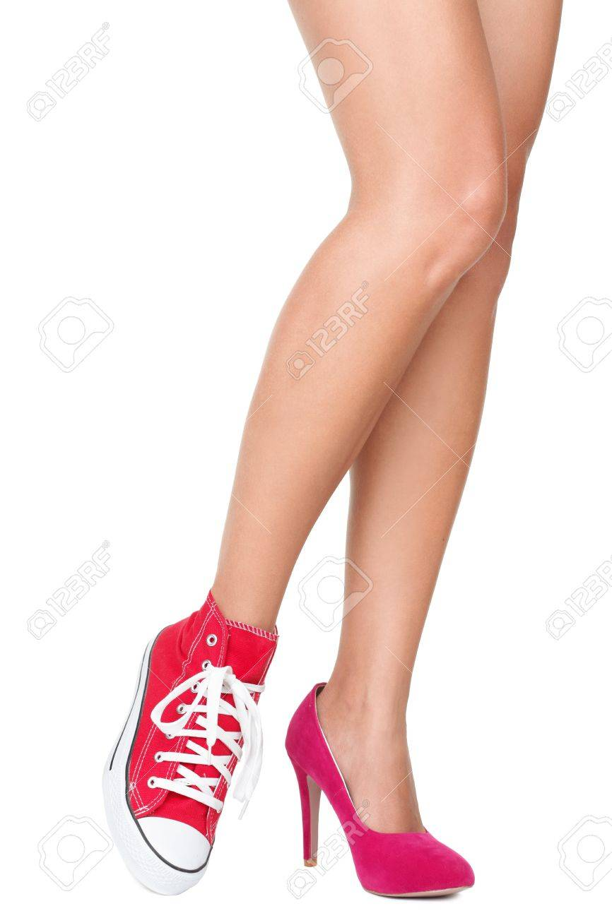 13585b26abc9 Stock Photo - Women shoes. Red high heels and sports shoes   sneakers.  Closeup of woman legs and feet wearing two different shoes.