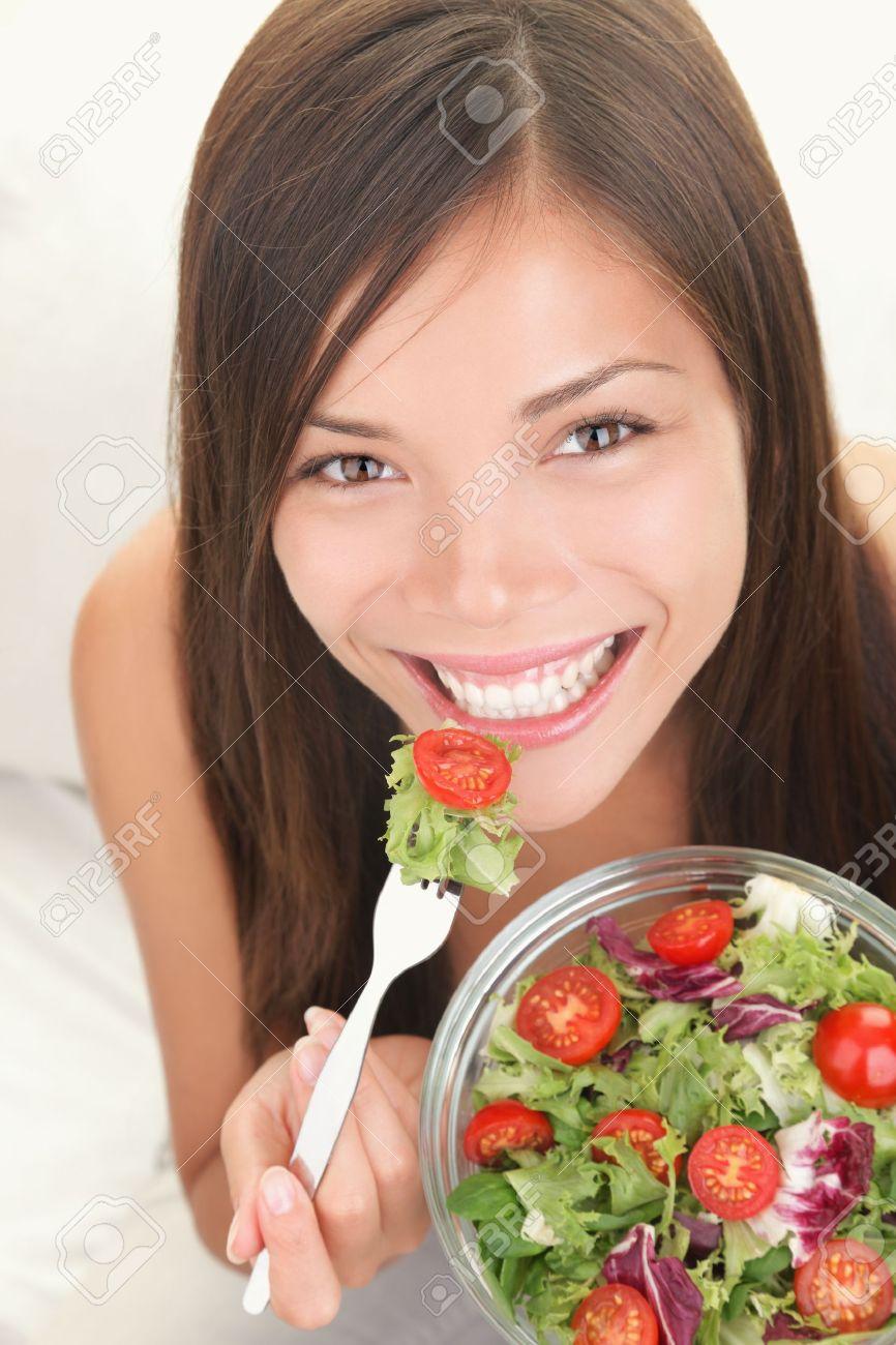 Salad. Portrait of healthy happy woman eating salad. Beautiful smiling Asian Caucasian female model. Stock Photo - 8361982