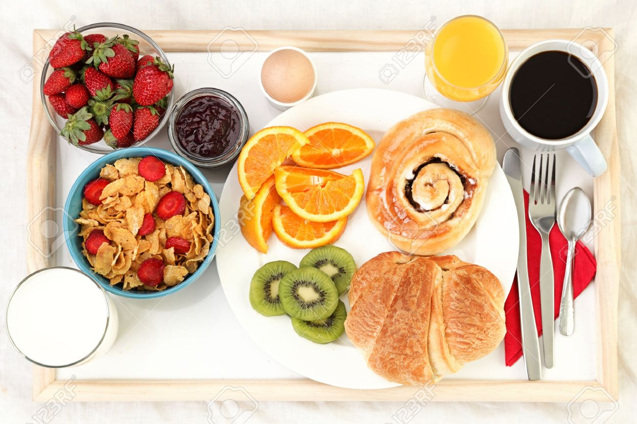 breakfast tray in bed with coffee, bread, cereals, fruit etc