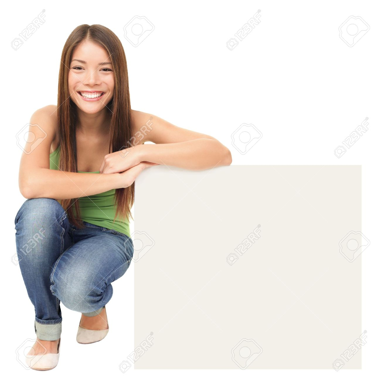 Woman sitting showing billboard sign. Cute casual young beautiful woman holding blank white commercial sign isolated on white background. Lovely fresh asian caucasian female model in full length. Stock Photo - 9091567